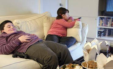 Overweight brother and sister sitting on a sofa