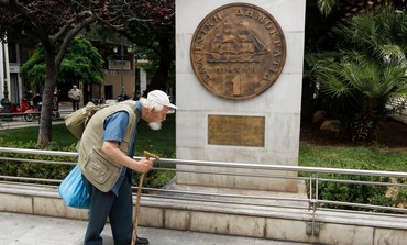 Greek man passes a drachma coin replica in Athens