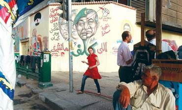 EGYPTIAN girl passes by graffiti