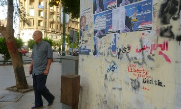 A man walks by a graffitied wall in DT Cairo