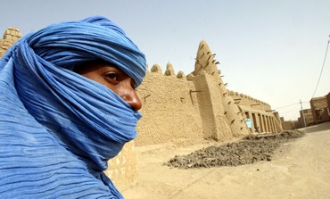 Tuareg nomad stands near 13th century mosque, Mali