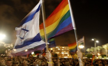 Pride flags being waved next to Israeli flags