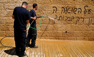 Workers cleaning graffiti at Yad Vashem