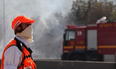 Rescue worker looks at Jerusalem fire