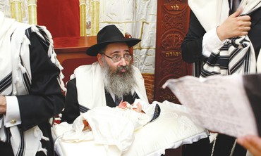 Rabbi holds boy for circumcision