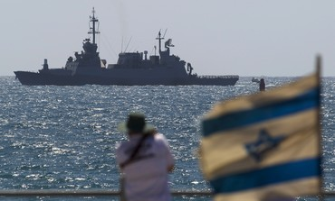 Man looks at Israeli Navy boat off Ashdod