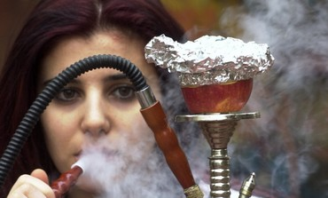 Woman smokes nargila from a hookah