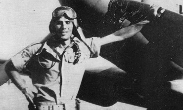 LOU LENART stands next to fighter plane