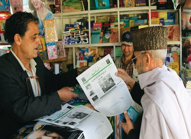 A MAN buys an 'Ensaf' newspaper at a kiosk in Kabu