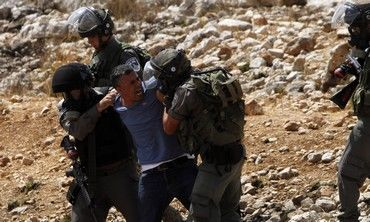 Security forces detain a Palestinian in Nabi Saleh