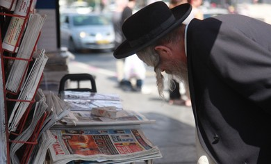 Man reads newspapers in Jerusalem.