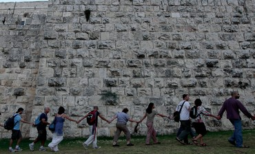 PEOPLE HOLD hands in front of Jerusalem's Old City