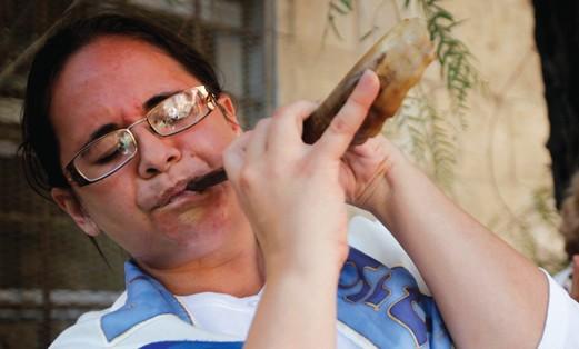 Lady blows a shofar