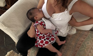 Mother breastfeeds her 2 month-old daughter