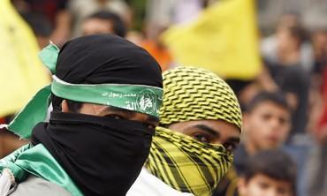 Palestinians wearing Hamas, Fatah masks