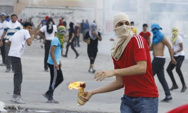 A SHI'A anti-government protester throws a Molotov