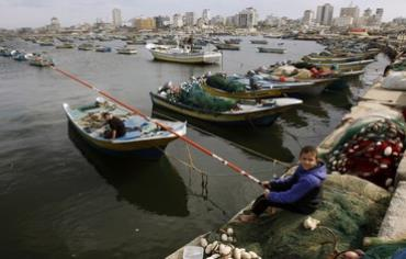A Palestinian boy fishes at the Gaza Seaport