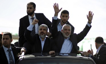 Hamas leader Khaled Mashaal [left] arrives in Gaza