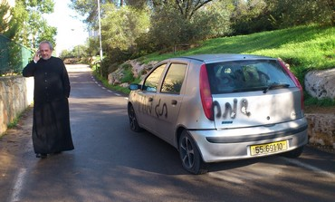Father Claudio near spray-painted car