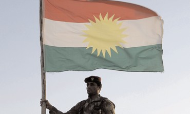 Kurdish soldier holding flag.
