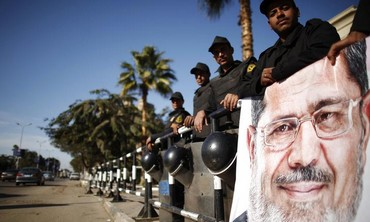 Policemen stand guard near Morsi poster, December 23, 2012