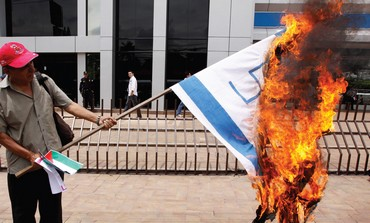 Protester burns Israeli flag with swastika on it in El Salvador