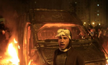 A protester stands in front of a burning riot police vehicle after it was seized in Cairo, Jan 28
