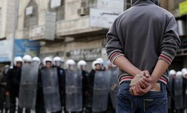 A Palestinian protester stands near Palestinian riot police, February 22, 2013.