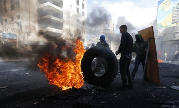Palestinian protesters next to burning tyre in Hebron