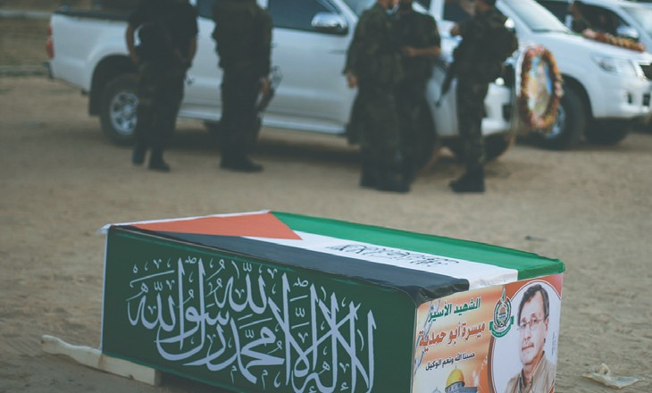 HAMAS MILITANTS stand near a mock coffin of Maissara Abu Hamdiyeh.
