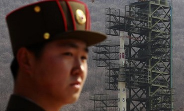 A soldier stands guard in front of the Unha-3 rocket in Pyongyang April 8, 2012.