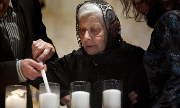 A Holocaust survivor lights a candle uring the Holocaust Remembrance Day in New York April 7, 2013.