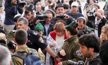 Law enforcement officials escort Women of the Wall Director Lesley Sachs.
