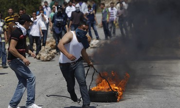 A Palestinian protester pulls a burning tire during a protest outside the village of Silwad