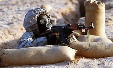 A Syrian soldier fires an AK-47.