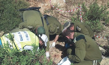 ZAKA AND MDA personnel work at the scene of a terror attack at the Tapuah Junction
