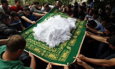 Family cover the body of a victim of the Syria conflict