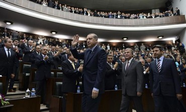 Turkish Prime Minister Erdogan waves at his parliament.