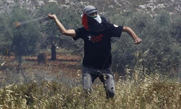 Palestinian uses sling to throw rocks at IDF near Deir Jarir in the West Bank, May 17, 2013.