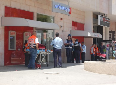 Police and EMS workers outside Beersheba bank where shooting took place, May 20, 2013