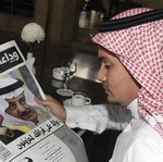 A man reads a newspaper in Jeddah June 17, 2012