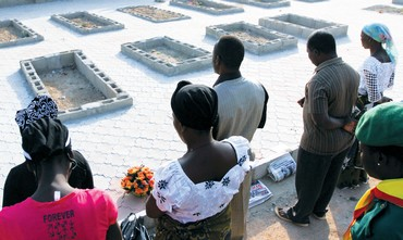 NIGERIAN MOURNERS at the graves of loved ones killed by a Boko Haram suicide bombing.