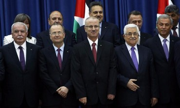 PA President Mahmoud Abbas (front row R) stands next to PM Rami Hamdallah (C) at  swearing-in