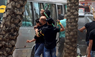 Hezbollah supporters attack a bus carrying anti-Hezbollah protesters in front of the Iranian embassy