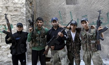 Brothers who are members of a rebel group called Martyr Al-Abbas pose for a picture in Aleppo.