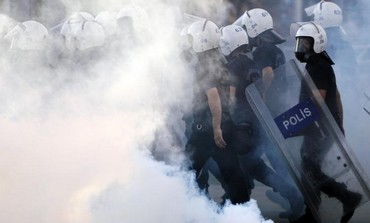 Police walk amidst tear gas during protests at Kizilay square in central Ankara, June 16, 2013.