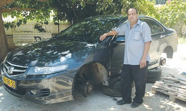 IBRAHIM SULEIMAN stands in front of his vandalized vehicle in Abu Ghosh
