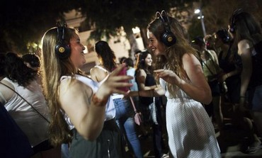 "Women dance during a ""Silent Disco"", in Tel Aviv during the ""White Night"" festival June 30, 2011"