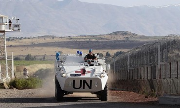 UN peacekeeping soldiers drive past an observation tower near the Quneitra border crossing