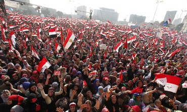 Protesters against Egyptian President Mohamed Morsi wave national flags
